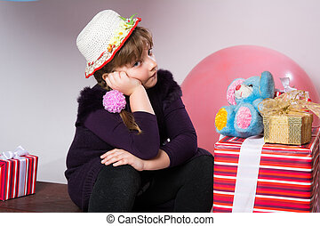 Teenage girl in a hat with gifts and toys. The girl sits on...