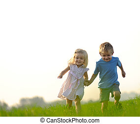 Free and happy - Brother and sister playing together in a...