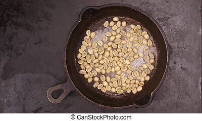 Grains of coffee are fried in a frying pan, stop motion,...