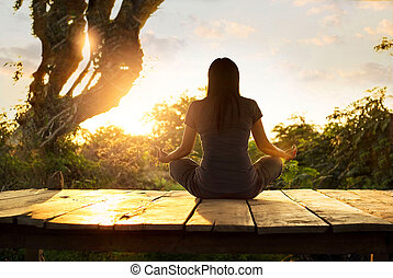 Woman practicing meditation yoga on the nature at sunset.