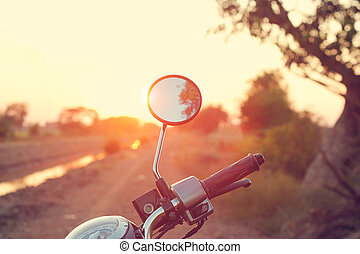Rearview mirror of motorcycle on dirt road in countryside