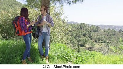Couple on rest while hiking - Young couple with backpacks...