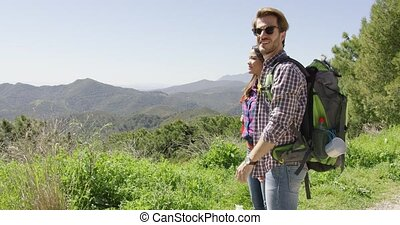 Young couple hiking in mountains - Two young people hiking...