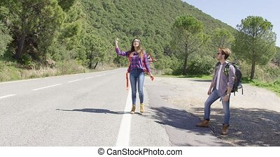 Young travellers hitch hiking on road - Young male and...