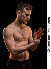 Fighter man with red boxing bandages on black background
