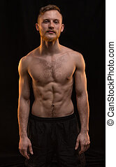 Young blond man with muscular body on black background