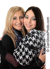 Portrait of two attractive girls embracing. Isolated