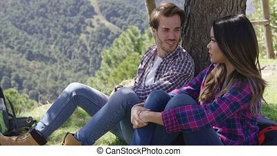 Sweet couple under tree - Young couple sitting under tree in...
