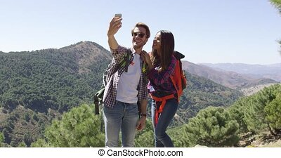 Young couple making selfie while hiking - Two young smiling...
