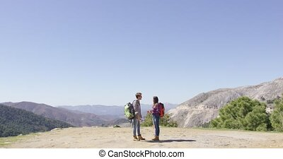 Two people standing on mountain plat - Two people with...