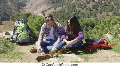 Couple sitting on ground in mountains - Laughing couple...