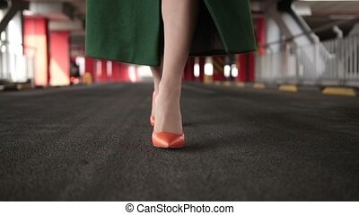 Woman's legs in high heel shoes walking on road - Closeup...