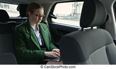 Serious businesswoman working in car on laptop - Serious...