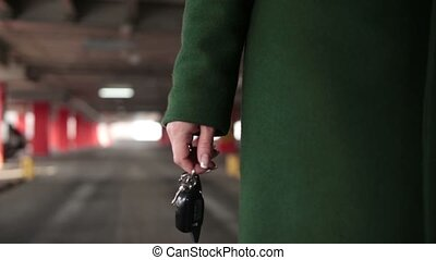 Female hand holding car key with remote control - Closeup...