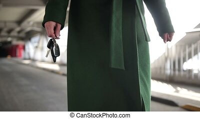 Woman holding modern car key walking to the car - Closeup...