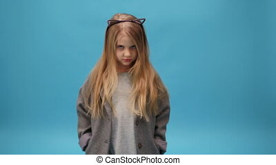 Young girl furrows her eyebrows - sad young girl on a blue...