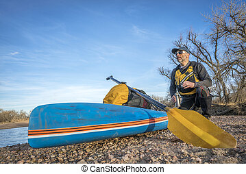 stand up paddling on a river - a senior male paddler is...
