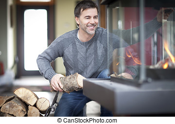 Mature man smiling at the country house. At the Fireplace -...