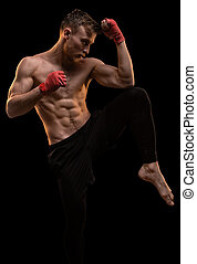 Muscular man during workout on black background