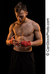 Boxer with red boxing bandages on black background