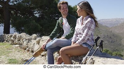 Young couple sitting on rocks in mountains - Young romantic...