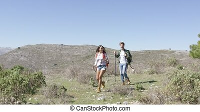 Two young people trekking - Young man and woman walking with...
