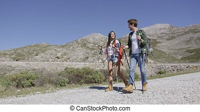 Young tourists walking down road - Two young tourists...