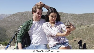 Smiling couple taking selfie in mountains - Young loving...