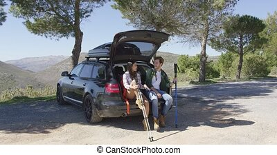 Two people sitting in trunk in mountains - Two young people...