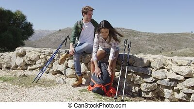 Two people trekking - Two young people setting backpacks and...