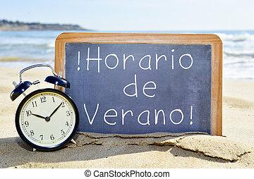 text horario de verano, summer time in spanish - an alarm...