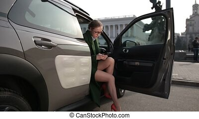 Busineswoman sitting in car using smartphone