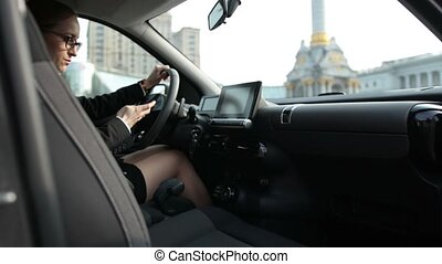 Business woman typing message on phone in car - Elegant...