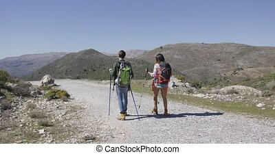 Back view of travellers in mountains - Back view of two...