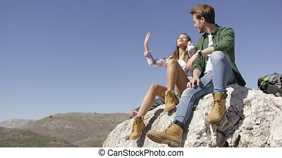 Two young tourists sitting on rock - Young couple sitting on...