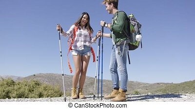 Two young happy travellers with trekking pole smiling and...