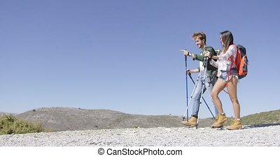 Funny couple walking with trekking poles - Young couple...
