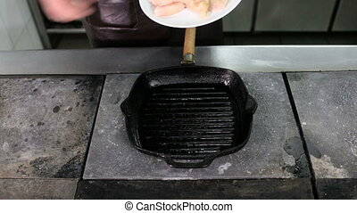 Two pieces of chicken fillet frying on a grill pan