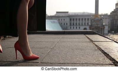 Woman's legs stepping down on stairway in city - Side view...
