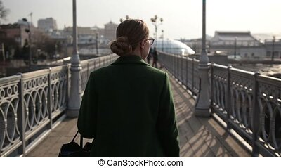 Back view of woman walking away on bridge - Back view of...