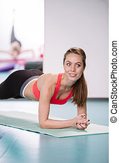 Sporty woman doing plank exercise in gym