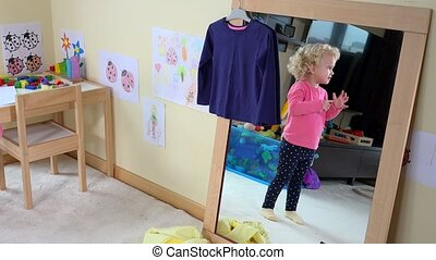 Cute girl measure clothes in front of mirror at home. Static...