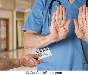 Senior doctor in scrubs refusing Medicare Card - Senior...