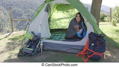 Smiling couple having fun in tent - Young smiling couple...