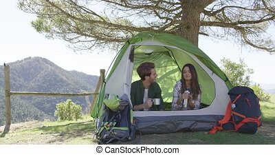 Smiling people having rest in tent - Young couple taking...