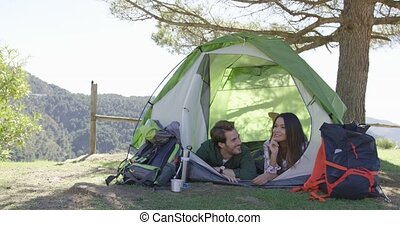 Smiling couple lying in tent and talking - Young loving...
