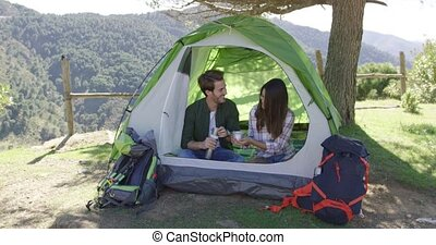 Two people having rest in tent - Young laughing couple...