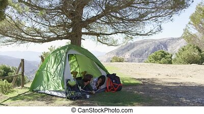 Romantic couple taking rest in tent - Two young travellers...