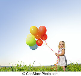 Colorful balloon girl - Adorable young girl holds tightly to...