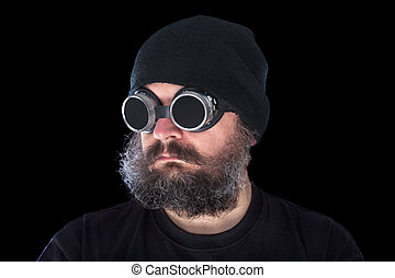 Weird guy with vintage welding goggles on black background -...